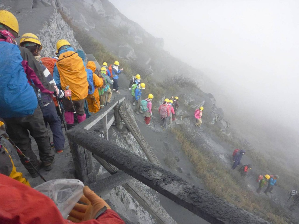 Climbers descend Mt. Ontake, which straddles Nagano and Gifu prefectures, to evacuate as volcanic ash falls at the mountain in central Japan
