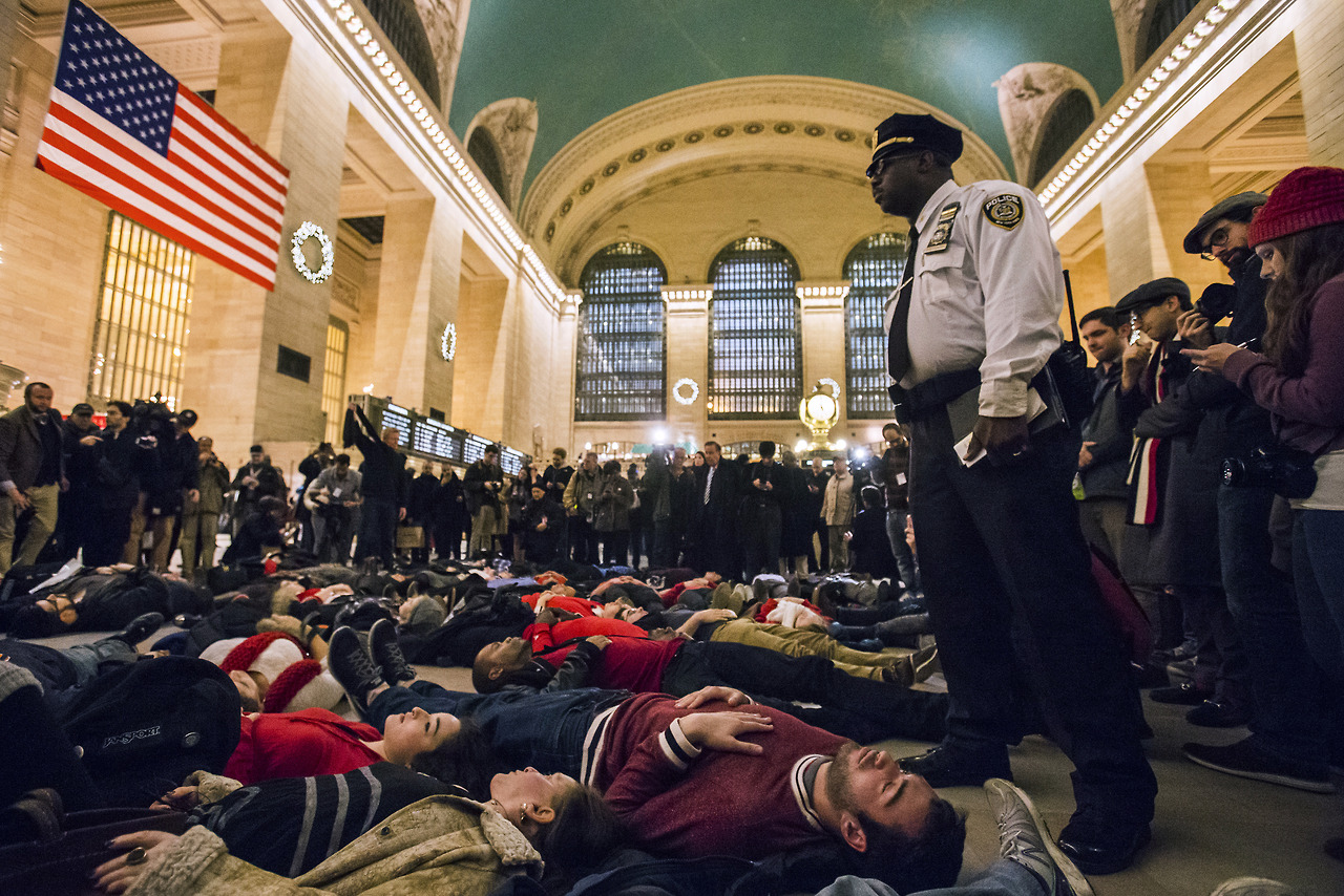 A police officer stands over activists, demanding justice for the death of Eric Garner, as they stage a 'die-in' during rush hour at Grand Central Terminal in the Manhattan borough of New York