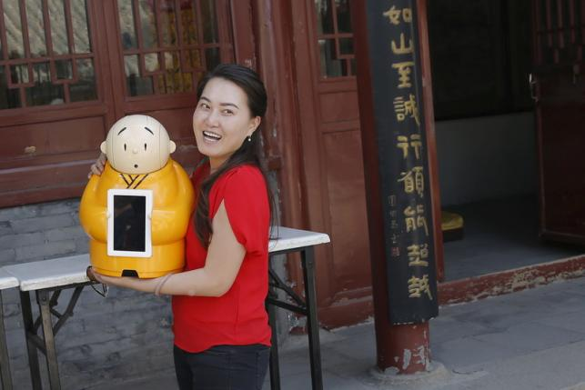 A visitor smiles as she holds Robot Xian'er which is placed in the main building of Longquan Buddhist temple for photograph by the temple's staff, on the outskirts of Beijing