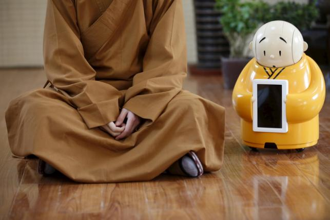 Robot Xian'er is placed next to Master Xianfan while Xianfan has an interview with Reuters at  Longquan Buddhist temple on the outskirts of Beijing